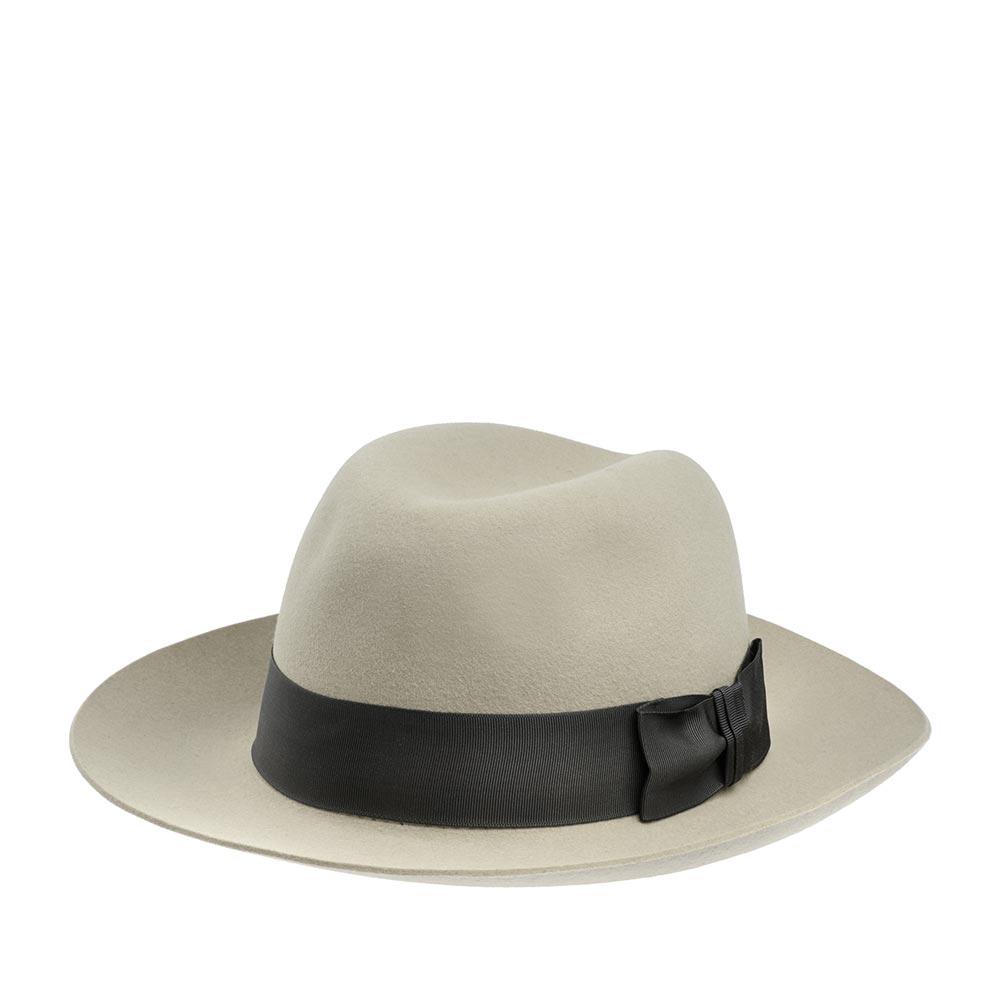 Шляпа федора CHRISTYSШляпы<br>Classic - роскошная, универсальная федора от Christys. Шляпа изготовлена вручную, в Англии, из материала высочайшего качества - пуха кролика. Тонкий, лёгкий головной убор очень комфортно садится на голову и удобен при ношении. Аксессур хорошо держит форму, поля зафиксированы в положении вверх, но их легко можно скорректировать по собственному желанию, изогнув переднее поле, или поля по кругу, вниз. Название Classic полностью оправдывает себя, это классический головной убор, сшитый в лучших традициях изготовления шляп. Тулья лаконично украшена репсовой лентой с бантом. Эта федора несёт дух туманной Великобритании, её исторически сложившуюся культуру каждодневного ношения головных уборов - снаружи дизайн максимально сдержан, а внутри Вы найдёте пришитую по окружности ленту из кожи, для удобной посадки на голову, и фирменную шелковистую подкладку ярко-красного цвета с логотипом производителя. На модель приятно смотреть даже когда Вы снимаете шляпу. Высота тульи - 11,5 см, ширина полей - 7 см.