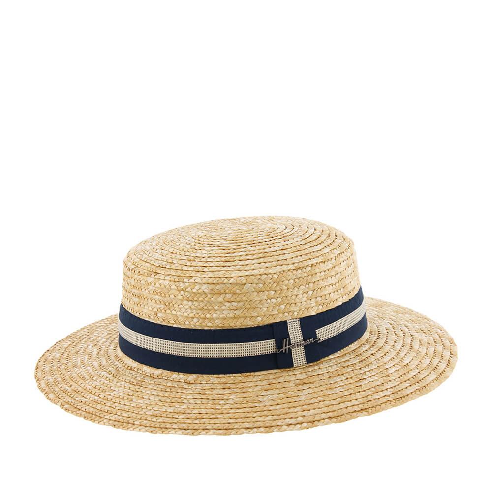 Шляпа канотье HERMANШляпы<br>Boater - элегантная шляпа канотье. Изготовлена из плоских соломенных косичек, свернутых и сшитых между собой в форме спирали. На широкую синюю ленту, которая украшает тулью, пришита более тонкая - бежево-коричневая с узором в мелкую клетку. На ленте сбоку перетяжка с логотипом бренда Herman. Натуральный материал шляпы хорошо защищает голову от перегревания. Шляпа отлично подойдет для загородной прогулки или для пляжного отдыха.